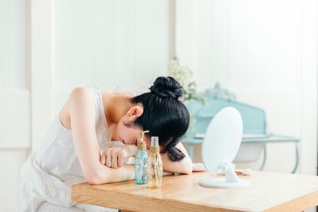 鏡の前で落ち込む女性
